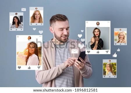 Handsome man visiting online dating site via smartphone on color background