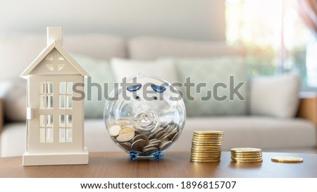 Property investment, house mortgage financial planning and real estate home refinancing concept with piggy bank saving budget and money coin stacks Royalty-Free Stock Photo #1896815707