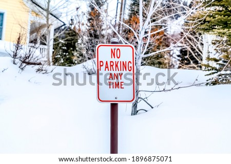 No Parking Anytime sign on a snow covered neighborhood landscape in winter