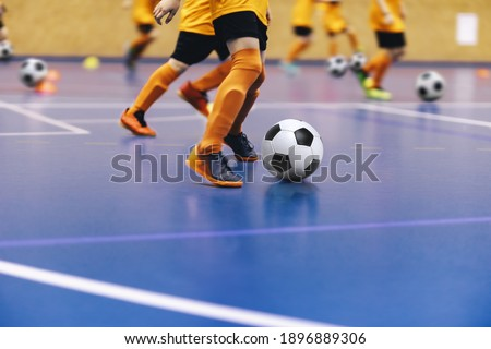 Indoor football training for youth team. Young boys with soccer balls running on wooden parquet. Indoor football soccer school practice. Kids in soccer sportswear Royalty-Free Stock Photo #1896889306