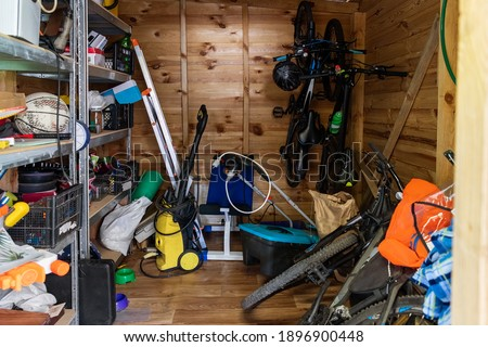 Suburban home wooden storage utility unit shed with miscellaneous stuff on shelves, bikes, exercise machine, ladder, garden tools and equipment. Messy and chaos at house yard barn. Organization order Royalty-Free Stock Photo #1896900448