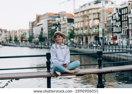 Full body of smiling positive female tourist sitting in lotus pose on bridge bench near river with historic buildings on embankment in Amsterdam Netherlands Royalty-Free Stock Photo #1896906055