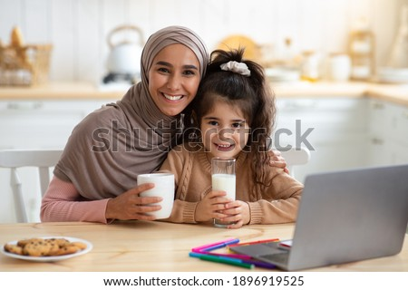 Happy Muslim Mom And Daughter Having Snacks And Drinks In Kitchen, Happy Islamic Lady In Hijab Enjoying Coffee And Her Cute Little Child Drinking Milk. Cheerful Family Smiling At Camera, Free Space Royalty-Free Stock Photo #1896919525