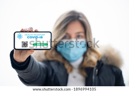 (Selective focus, focus on the smart phone) A defocused young girl, wearing a face mask, is holding a smart phone with a digital illustration of a Covid-19 Health Passport concept. Royalty-Free Stock Photo #1896994105