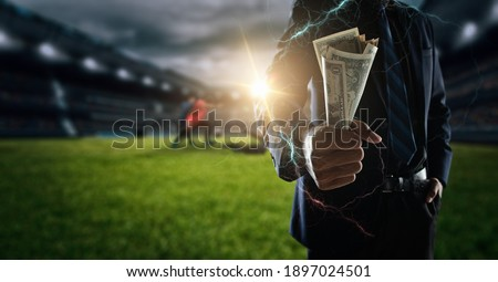 Concept of betting bet sport.businessman holding large amount of bills at Soccer stadium in background. Royalty-Free Stock Photo #1897024501
