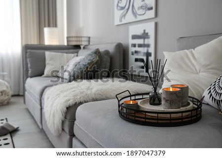 Candles and aroma reed diffuser on grey sofa, space for text Royalty-Free Stock Photo #1897047379