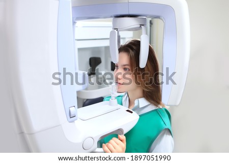 The girl in the X-ray room makes a panoramic picture of her teeth. Disease prevention and dental treatment. X-ray equipment. Panoramic image of teeth. Modern dentistry and medicine. Copy space.