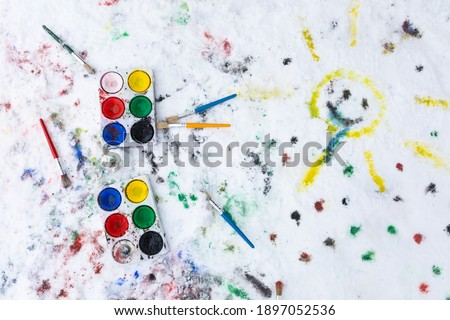 Watercolor painting on snow outdoors. Two water color paint boxes and paint brushes are seen from above. There is paint on the snow and a painted happy sun. Outdoors fun painting activity for families