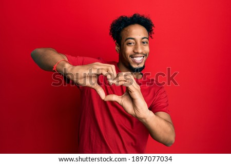Young african american man with beard wearing casual red t shirt smiling in love doing heart symbol shape with hands. romantic concept.