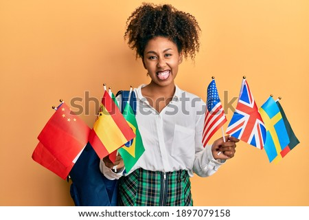 Beautiful african american woman with afro hair exchange student holding countries flags sticking tongue out happy with funny expression.