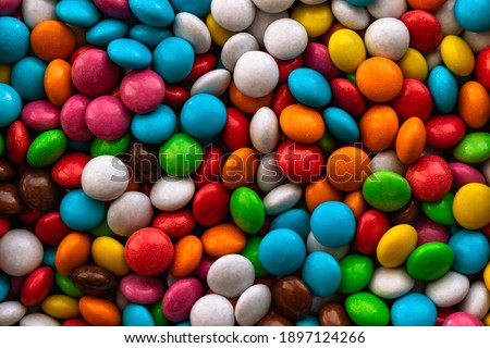 Background from a large number of multicolored sweets. Colorful set of flat sweets. Mix of colored sweets. Dragee sweets. Confectionery. Royalty-Free Stock Photo #1897124266