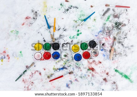 Watercolor painting on snow outdoors. Two water color paint boxes and scattered paint brushes seen from above. There is paint on the snow. Outdoors fun painting activity for families.