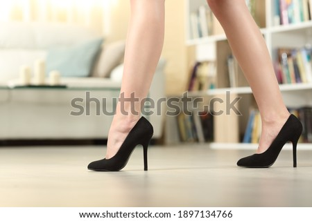 Profile of woman legs with high heels walking in the living room at home Royalty-Free Stock Photo #1897134766