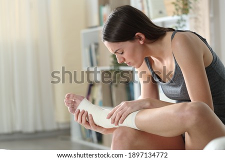 Disabled woman wearing bandaged feet complaining suffering ankle ache sitting on a couch at home Royalty-Free Stock Photo #1897134772