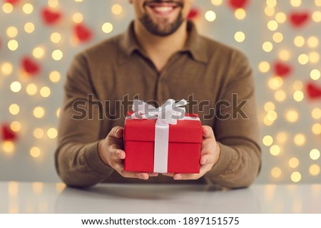 Cropped image close up of a red gift box with a white bow in male hands sitting at the table. Concept of gifts for birthday, Christmas, Valentine or Women's Day. Blurred background, selective focus.