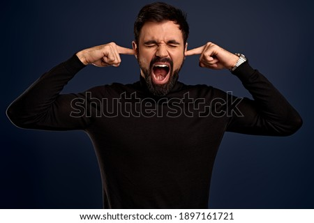 Photo of desperate annoyed bearded man keeps hands on head, shouts loudly, closes ears with his fingers, opens mouth, closes eyes, feels depressed, has many debts and financial crisis, wears sweater.