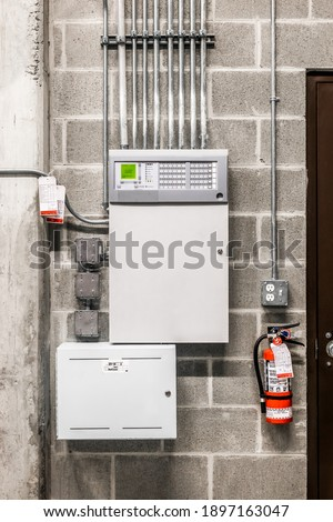 Fire alarm control panel, cabinet, fire extinguisher and service tags. Single-stage fire alarm system in electrical service room of residential or commercial building.  Royalty-Free Stock Photo #1897163047