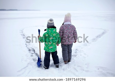 Boy and girl have fun and removing snow from the ice on the frozen lake in heart shape. Winter romantic, silence and wild nature, active winter weekend, outdoor activities, icy landscape, lifestyle Royalty-Free Stock Photo #1897169296