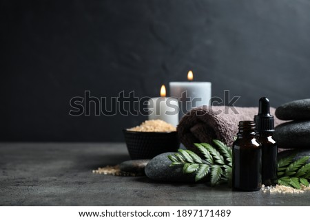 Spa composition with aroma oil on grey table, space for text Royalty-Free Stock Photo #1897171489