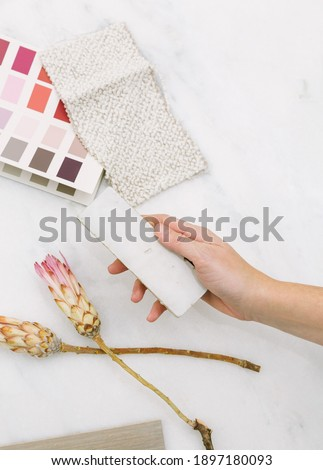 Interior designer selecting paint colors, fabric swatches, and tile samples. Overhead lay down on white marble surface with pink color story