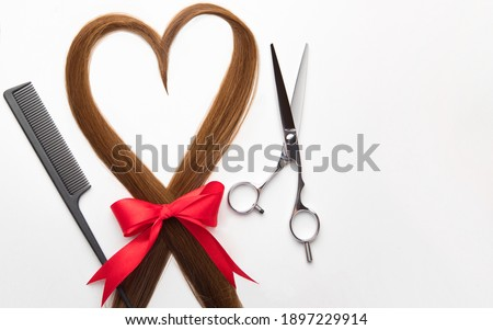 Scissors, comb and heart shaped hair lock. Professional barber hair cutting shears on white background. Hairdresser salon equipment, premium hairdressing set. Accessories for haircut. Valentines day. Royalty-Free Stock Photo #1897229914