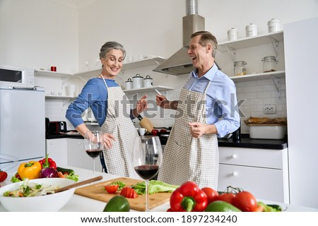 Happy active old senior mid aged 60s family couple enjoying dancing and cooking healthy meal together at home, having fun preparing romantic dinner, celebrating Valentines Day with wine in kitchen.