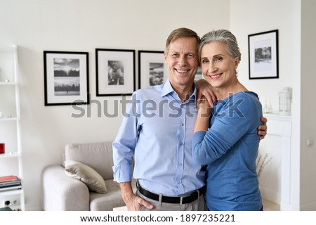 Happy senior mature 60s family couple hugging, looking at camera, standing in living room in modern apartment. Smiling satisfied middle aged husband and wife embracing posing for portrait at new home. Royalty-Free Stock Photo #1897235221