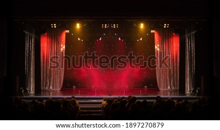 The stage of the theater illuminated by spotlights from the auditorium Royalty-Free Stock Photo #1897270879