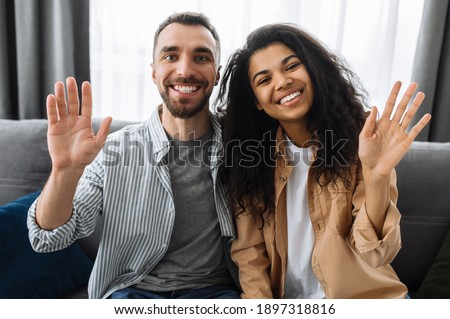 Multiracial couple in love, caucasian guy and african american girl, sitting on a sofa talk on video call with friends or family greeting, smiling and waving hands #1897318816