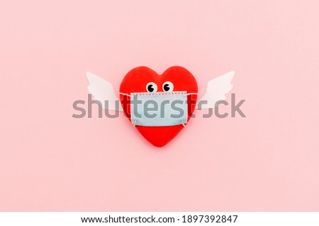 Heart with eyes and angel wings in protective masks on a pink background. Valentine's Day concept. Coronavirus pandemic concept.Flat lay, top view.