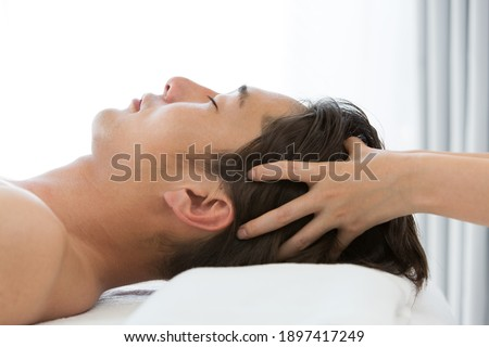 Young Asian men are head massaged. Royalty-Free Stock Photo #1897417249