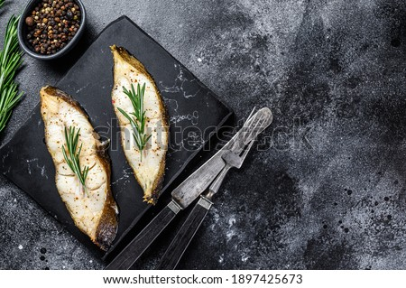 Halibut fish steak with rosemary. Black background. Top view. Copy space.