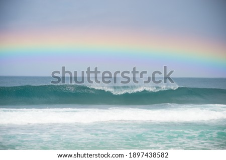 A rainbow over the waves Royalty-Free Stock Photo #1897438582
