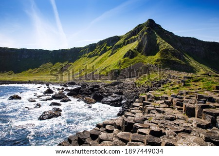 Landscape of Giant's Causeway trail with a blue sky in summer in Northern Ireland, County Antrim. UNESCO heritage. It is an area of basalt columns, the result of an ancient volcanic fissure eruption Royalty-Free Stock Photo #1897449034