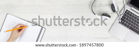 Laptop. keyboard and headphones on grey desk. hand with pencil notebook. Helpdesk or call center headset. Distant learning or working from home, online courses or support center concept. Wide banner Royalty-Free Stock Photo #1897457800