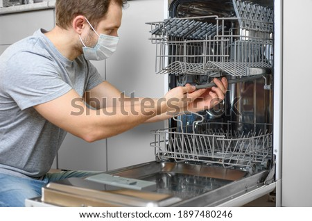 Man repairing a dishwasher with tools Royalty-Free Stock Photo #1897480246