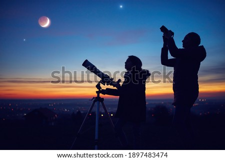 Mother and daughter observing stars, planets, Moon and night sky with astronomical telescope. Royalty-Free Stock Photo #1897483474