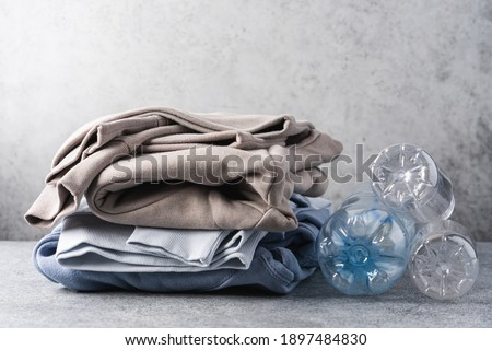 Stack of trendy modern clothes made from recycled plastic. Eco products and zero waste concept Royalty-Free Stock Photo #1897484830