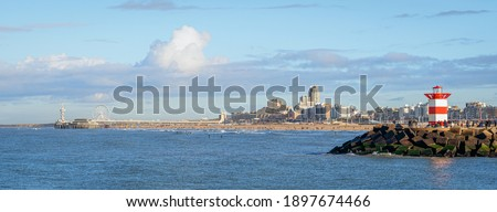 Panoramic view over Scheveningen Pier, beach, and harbor entrance with a lighthouse on a very clear day in January Royalty-Free Stock Photo #1897674466