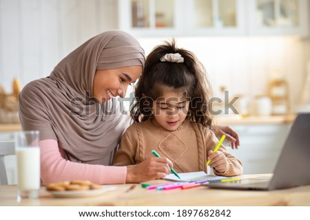 Loving Muslim Mom In Hijab Drawing With Her Little Preschooler Daughter In Kitchen, Happy Islamic Family Sitting At Table And Using Colorful Pencils, Having Fun Together At Home, Free Space Royalty-Free Stock Photo #1897682842