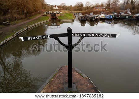 Canal sign post for the stratford and grand union canal. Narrow boats moored up on the canal