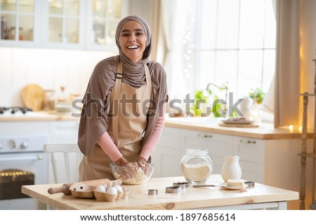 Baking Concept. Portrait Of Joyful Muslim Woman In Hijab Kneading Dough In Kitchen Interior, Cheerful Islamic Female In Hijab And Apron Having Fun While Preparing Homemade Pastry, Laughing At Camera Royalty-Free Stock Photo #1897685614