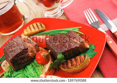 roast meat : beef (pork) steak garnished with vegetables , juice and olives on red plate over wooden table #189769088
