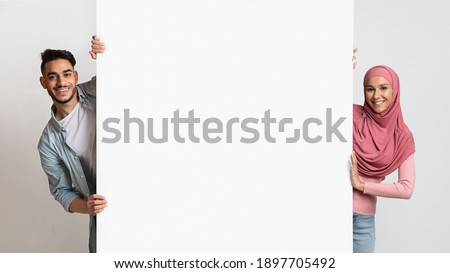 Smiling young muslim couple holding white advertisement board, demonstrating free copy space for your text or design, positive arab man and woman in hijab standing over grey background, panorama Royalty-Free Stock Photo #1897705492