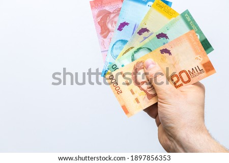 Costa Rican money, Colones, All banknotes fanned and held in a male hand, White background, Place for text Royalty-Free Stock Photo #1897856353