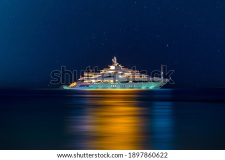 Night view to large illuminated white boat located over horizon, colorful lights coming from yacht reflect on the surface of the the Gulf sea. Shot at blue hour.   Royalty-Free Stock Photo #1897860622