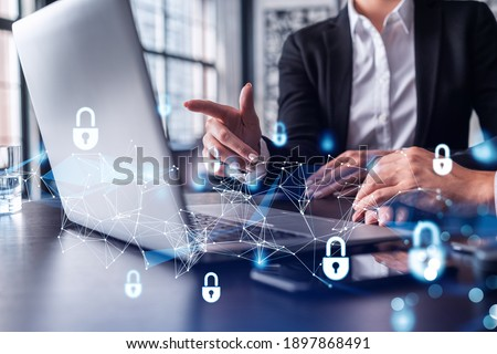 Two business people working on the project to protect cyber security of international company using laptop. Padlock Hologram icons. Teamwork concept.