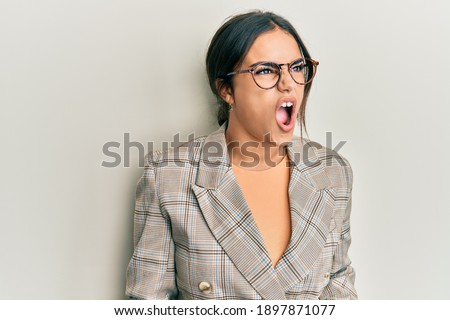 Young brunette woman wearing business jacket and glasses angry and mad screaming frustrated and furious, shouting with anger. rage and aggressive concept.  Royalty-Free Stock Photo #1897871077