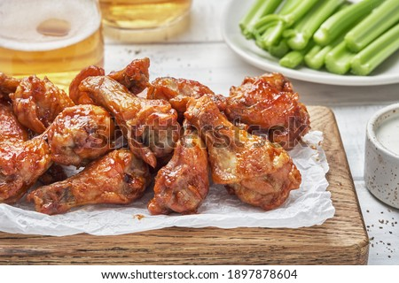 buffalo chicken wings with celery and beer Royalty-Free Stock Photo #1897878604