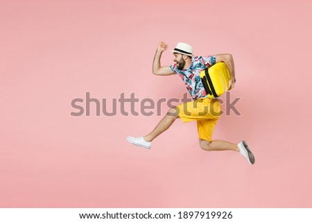 Full length side view of cheerful traveler tourist man in summer clothes hat jumping running hold suitcase isolated on pink background. Passenger traveling on weekend. Air flight journey concept Royalty-Free Stock Photo #1897919926